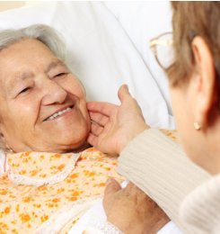caregiver touching the face of elderly patient
